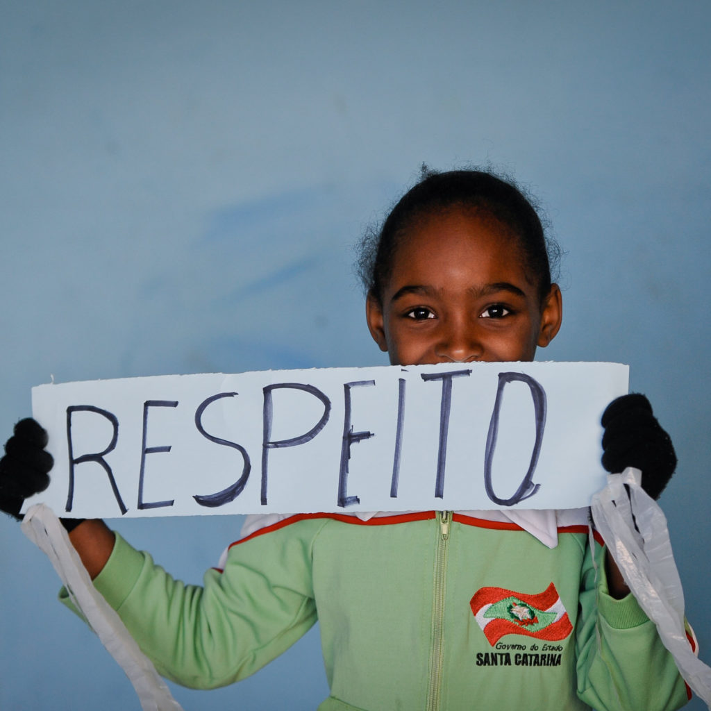 """Criança negra com uniforme escolar segurando um cartaz feito à mão que diz: """"Respeito"""". No fundo um céu azul."""