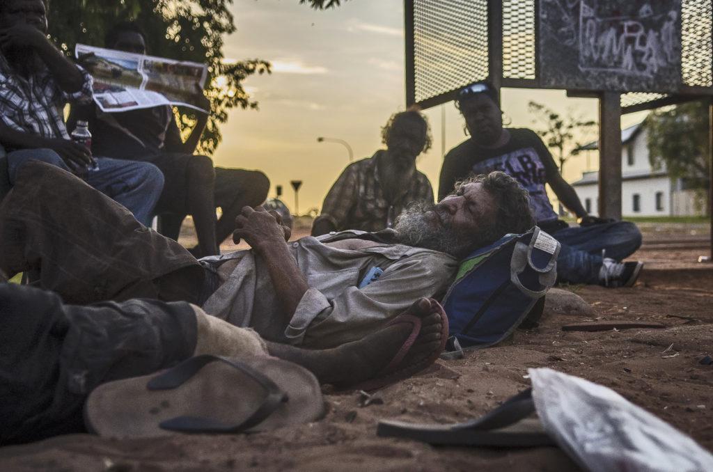 Homens negros deitados na rua como indigentes.