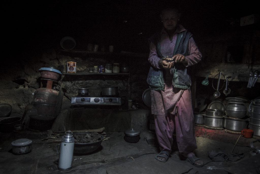 cozinha escura com uma pessoa ao fundo com o rosto escondido pela escuridão.