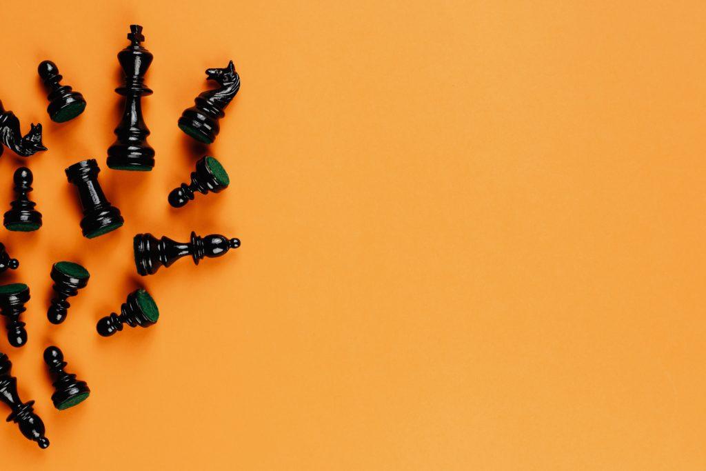 Fundo amarelo com peças de xadrez pretas no canto esquerdo da imagem