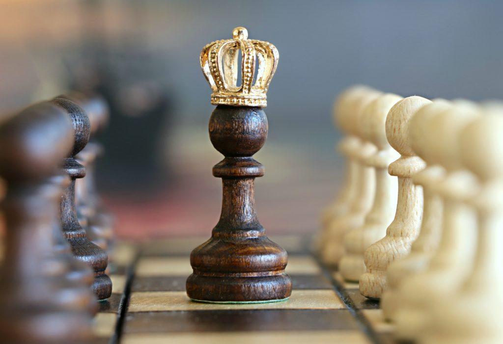 Tabuleiro de xardrez com destaque para um peão com coroa dourada.