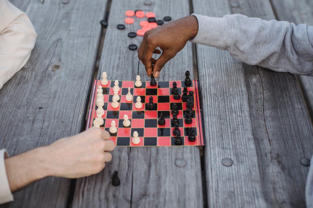 Duas pessoas jogando xadrez, sendo uma negra e outra branca, simulando a ideia de diversidade corporativa na estratégia