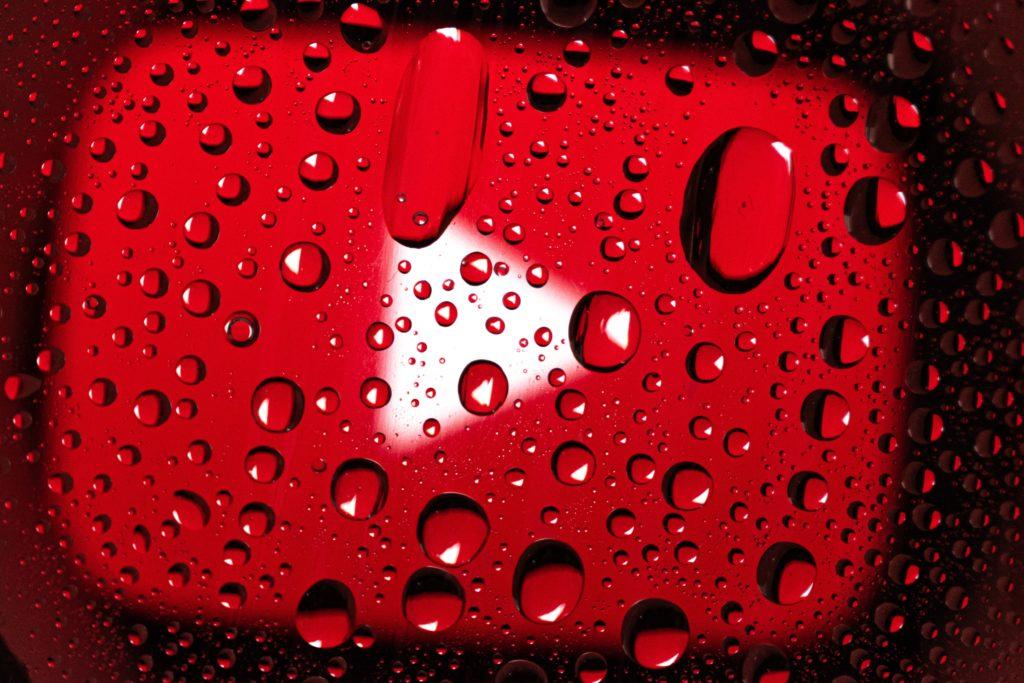fundo vermelho com tri§angulo branco formando a marca do youtube com gotas de água em cima.